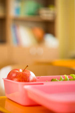 lunchtime: Food container with apple and salad in classroom