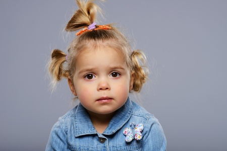 dissapointed: Disappointed little girl isolated on grey background