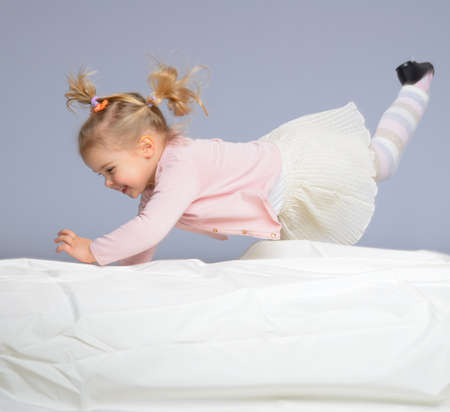 child in bed: Happy little girl having fun on bed isolated on grey Stock Photo