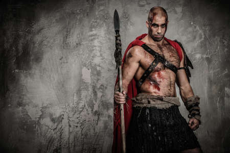 spears: Wounded gladiator in red coat holding spear Stock Photo