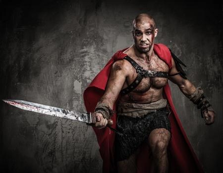 romano: Gladiador herido atacar con la espada cubierta de sangre