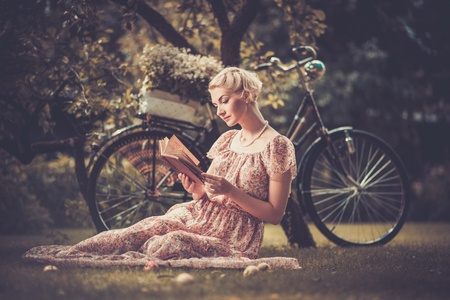 bikes: Blond beautiful retro woman reading book on a meadow Stock Photo