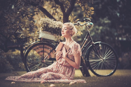femme romantique: Rêver rétro femme blonde avec un livre assis sur une prairie