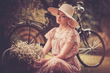 femme romantique: Belle rétro femme avec panier de fleurs n et de vélos derrière elle Banque d'images