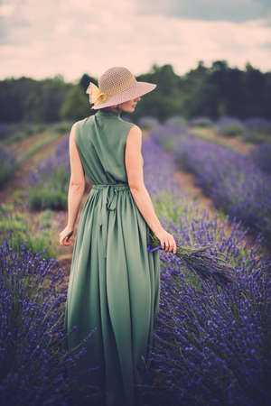 field flower: Woman in long green dress and hat in a lavender field Stock Photo