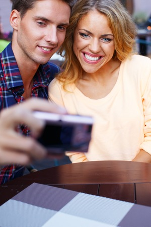 Young couple taking picture of themselves in summer cafe photo