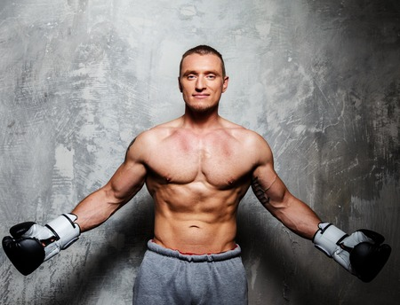 muscular men: Young sporty man in boxing gloves posing