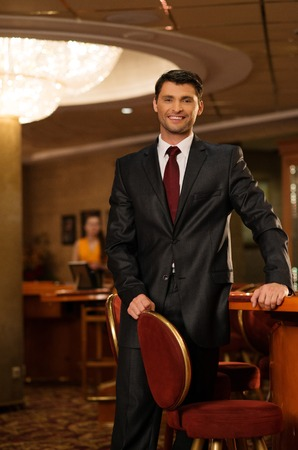 Handsome smiling brunette wearing suit in luxury interior  photo