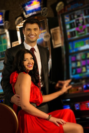 man machine: Beautiful young couple near slot machine in a casino Stock Photo