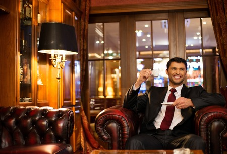 Handsome smiling brunette sitting with a cup of coffee in a luxury interior  photo