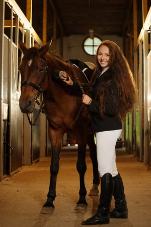 Beautiful girl with her horse in a stall  photo