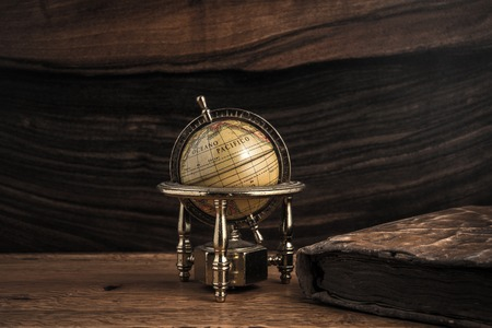 Vintage book and little globe on a wooden background  photo