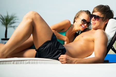 sexy young couple: Sexy young couple relaxing on a beach bed Stock Photo