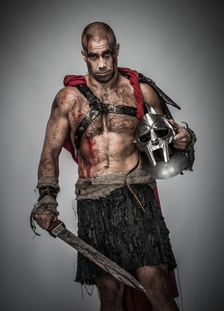 Wounded gladiator with sword covered in blood and helmet isolated on grey photo
