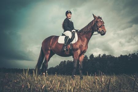 parapente: Bella joven sentado en un caballo al aire libre contra el cielo cambiante