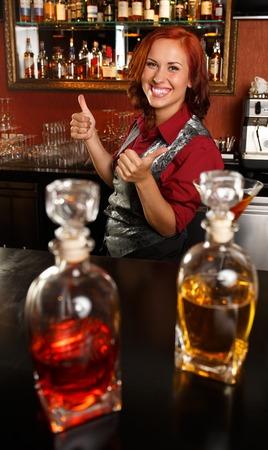 Beautiful redhead barmaid behind bar counter  photo