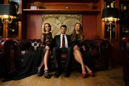 wealthy lifestyle: Handsome bruna indossa tuta seduta sul divano con due belle donne Archivio Fotografico