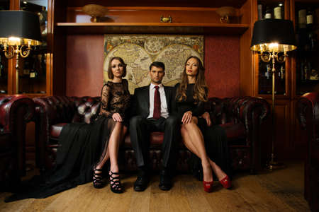 costly: Handsome brunette wearing suit sitting on sofa with two beautiful women