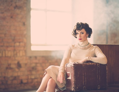 Beautiful vintage style young woman with suitcase on a train station photo