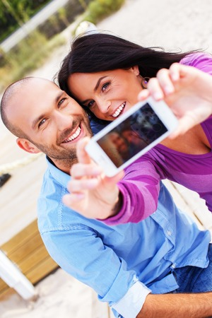 Happy smiling middle-aged couple on a beach taking photo of themselves  photo