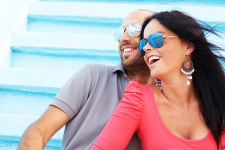 Happy smiling middle-aged couple with beach reflected in sunglasses photo