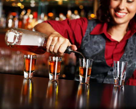 Beautiful redhead barmaid making shots photo