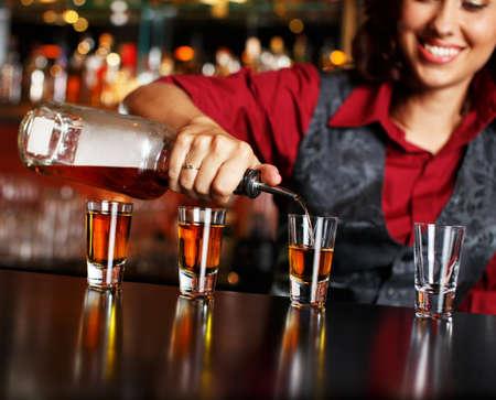 botella de whisky: Hermosa camarera pelirroja haciendo disparos Foto de archivo