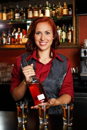 Beautiful redhead barmaid making shots photo