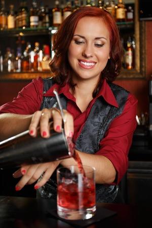 Beautiful redhead barmaid making cocktail photo