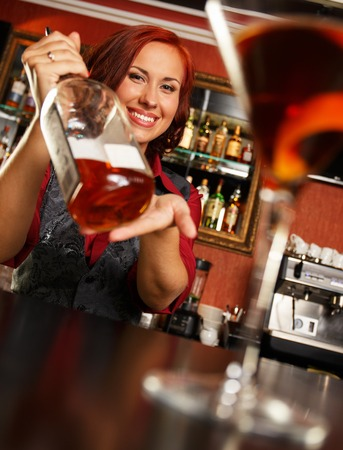 vodka bottle: Beautiful redhead barmaid with bottle behind bar counter