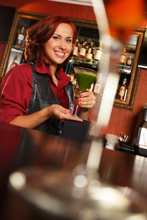 Cheerful barmaid with cocktail behind bar counter  photo