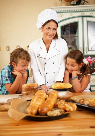 Mother cook with her little children preparing homemade pastry photo