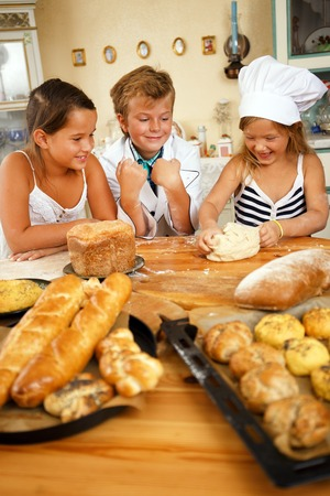 children cooking: Happy children cooking homemade pastry