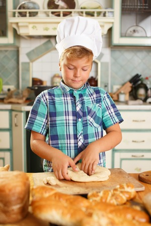 Young cook boy making homemade pastry photo