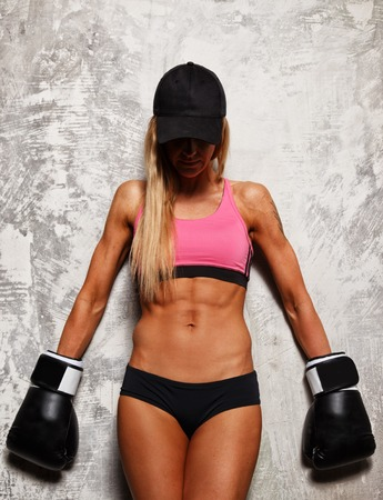 Sporty woman in pink top and boxing gloves with beautiful beautiful body against concrete wall photo