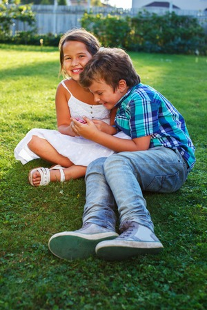 Happy children sitting on a meadow with mobile phone photo