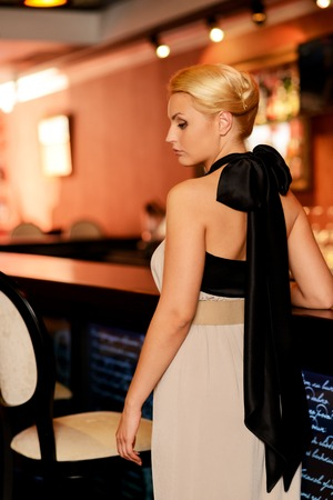Beautiful blond woman in evening dress standing near bar counter photo