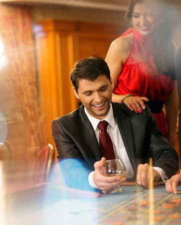 win money: Beautiful young couple behind roulette table in a casino Stock Photo