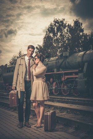 Beautiful vintage style couple with suitcases on  train station platform photo