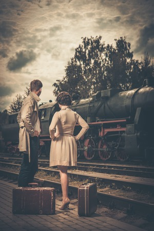 railway history: Beautiful vintage style couple with suitcases on  train station platform