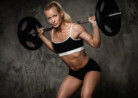 body pump: Beautiful muscular bodybuilder doing exercise with weights