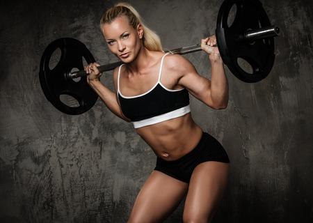rejas de hierro: Culturista muscular hermosa que hace ejercicio con pesas