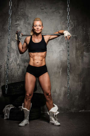 Beautiful muscular bodybuilder woman with a big hammer  photo