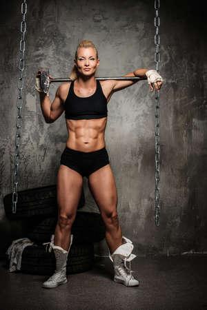 Beautiful muscular bodybuilder woman with a big hammer
