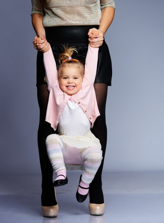 Mother swinging her happy little daughter  photo