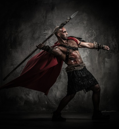 warrior: Wounded gladiator in red coat throwing spear Stock Photo