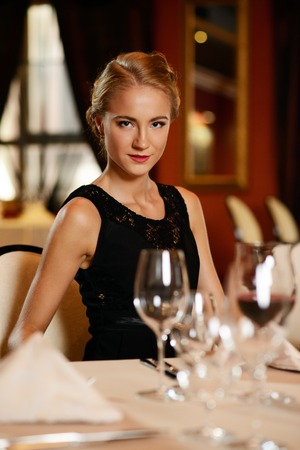 Beautiful young girl alone in a restaurant photo