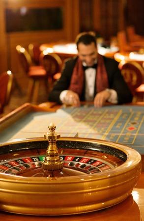 ruleta de casino: El hombre en traje y bufanda jugando a la ruleta en un casino Foto de archivo