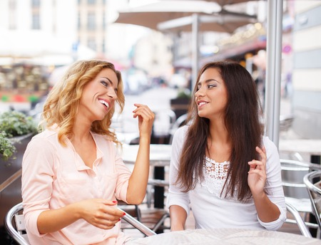 Two beautiful girls chatting in summer cafe  photo