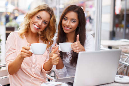 Two beautiful girls cups and laptop in summer cafe photo